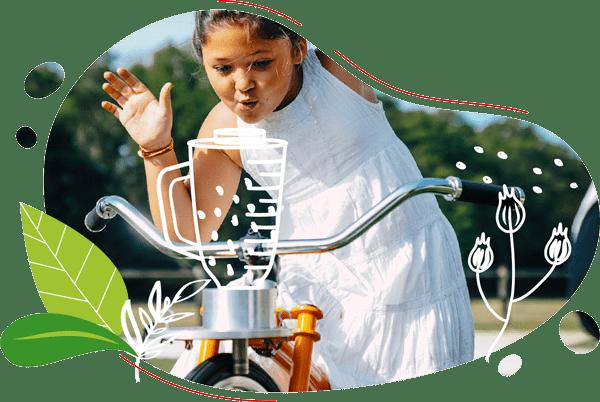 photo d'une petite fille en robe blanche en train de pédaler un smoothie sur son vélo